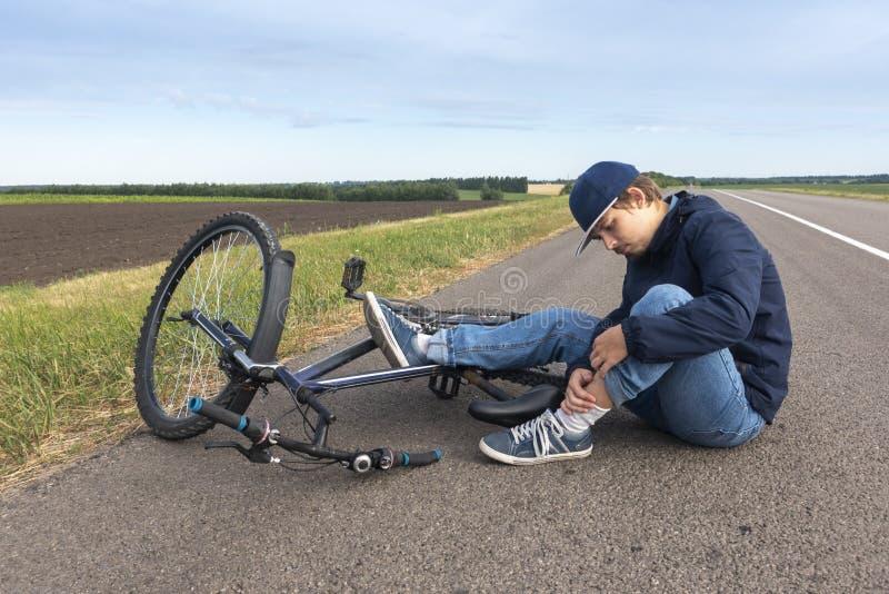 Мальчик сидит в дороге после падать от велосипеда, утихомиривает боль в ее колене стоковое изображение