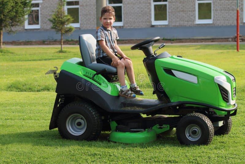 Мальчик сидит на лужайке на зеленой траве стоковое фото