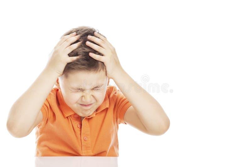 Мальчик сидит на таблице, держа его голову с его руками Конец-вверх, открытый космос для текста o стоковые фото