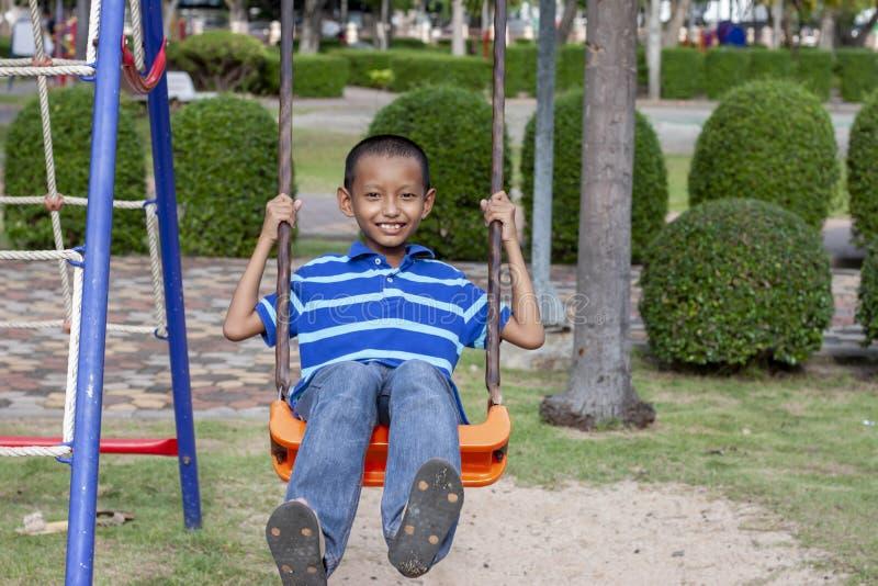 Мальчик сидя в качаниях со счастливой улыбкой на спортивной площадке стоковое фото