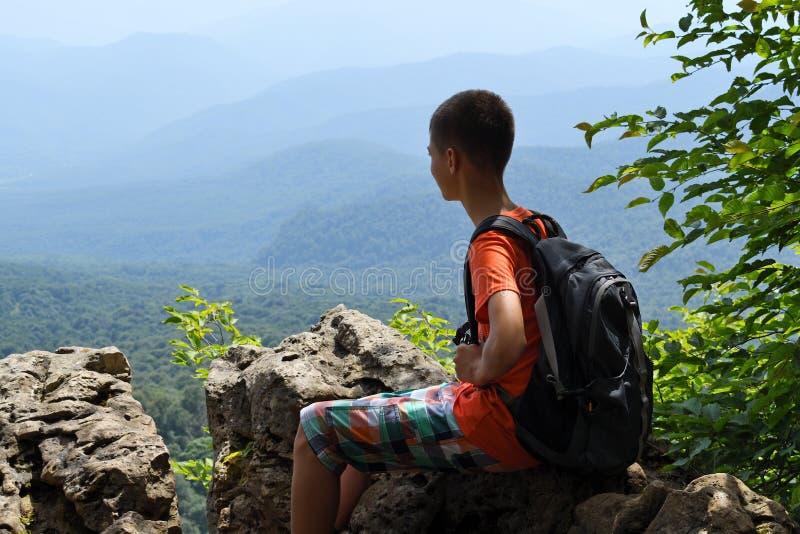 Мальчик сидя на крае скалы с рюкзаком стоковое фото rf