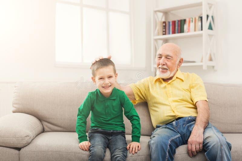 Мальчик сидя на кресле с его дедом стоковое фото
