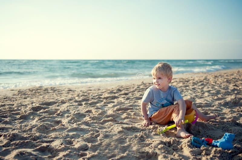 Мальчик сидя на пляже стоковое изображение