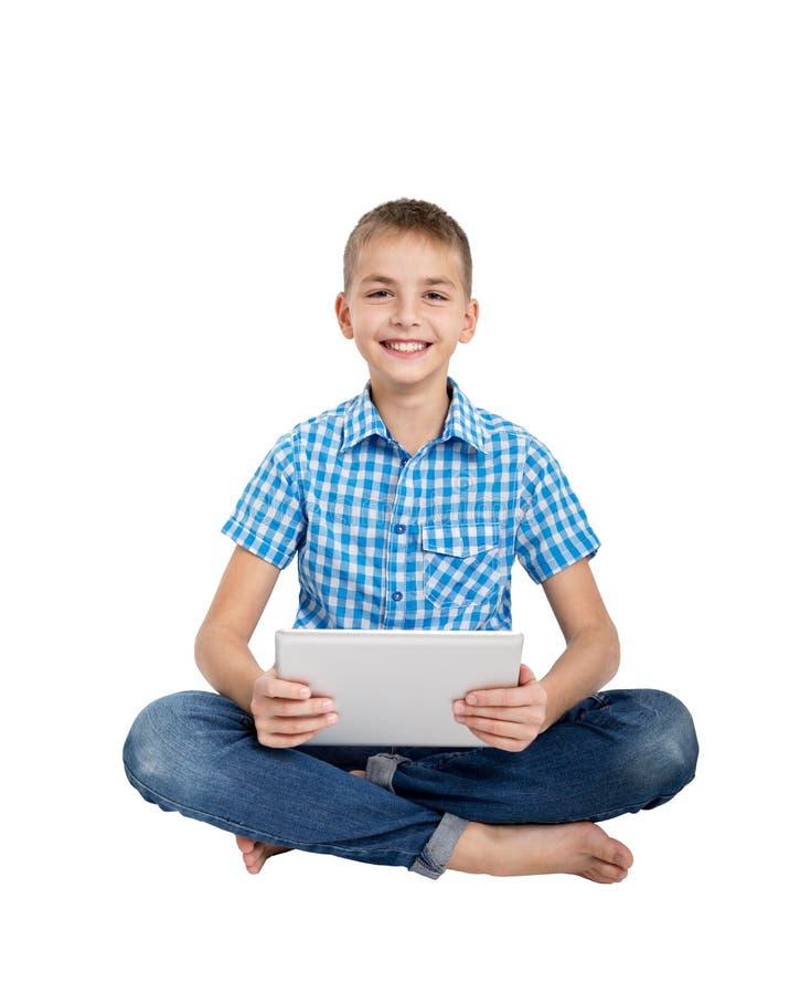 Мальчик сидя с таблеткой цифров стоковые фотографии rf
