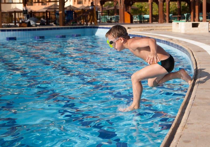 Мальчик скача в бассеин стоковое изображение