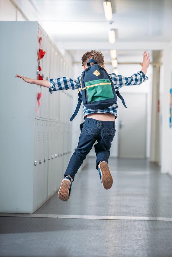 мальчик скача в коридор школы стоковое фото