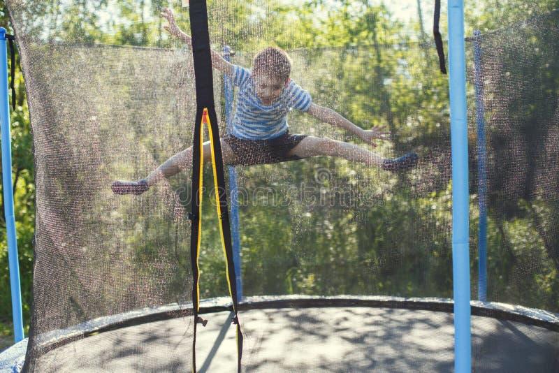 Мальчик скача на батут детские игры на батуте стоковые изображения