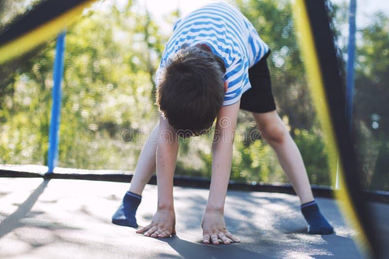 Мальчик скача на батут детские игры на батуте стоковые фото