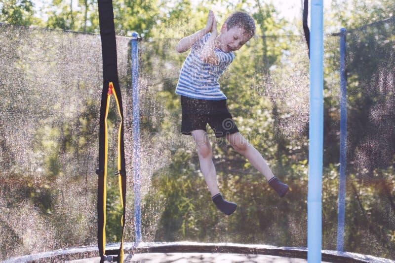 Мальчик скача на батут детские игры на батуте стоковое фото rf
