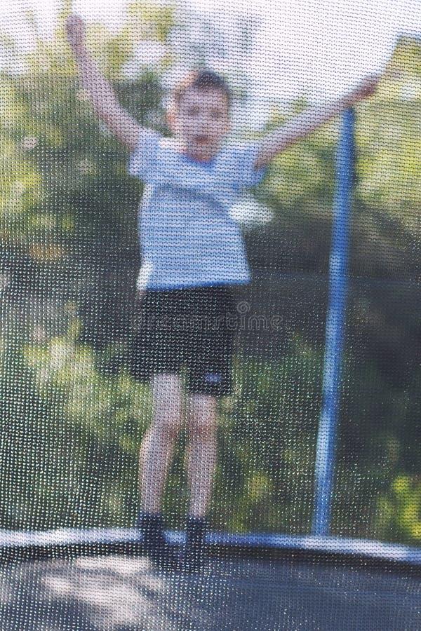 Мальчик скача на батут детские игры на батуте стоковая фотография