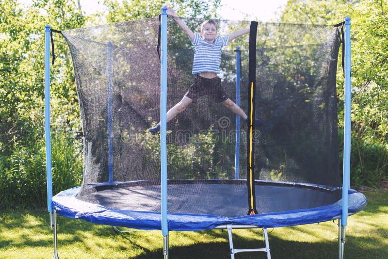 Мальчик скача на батут детские игры на батуте стоковая фотография rf