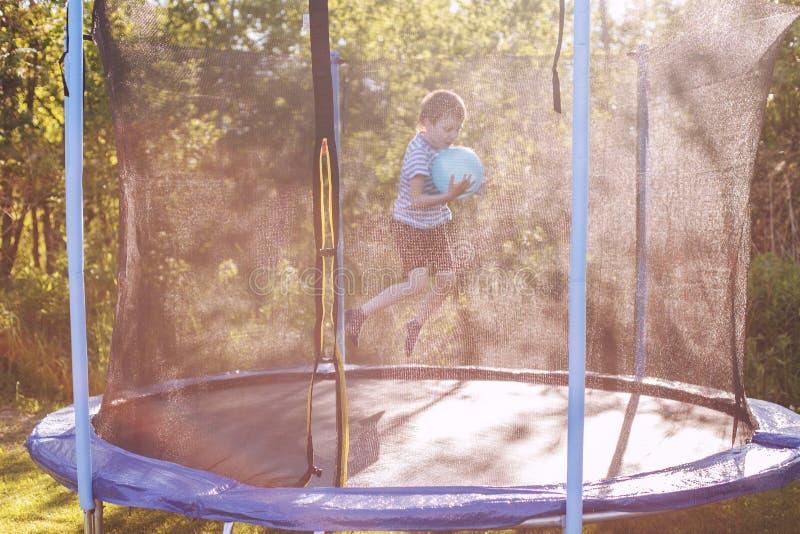 Мальчик скача на батут ребенок играя с шариком стоковые фотографии rf