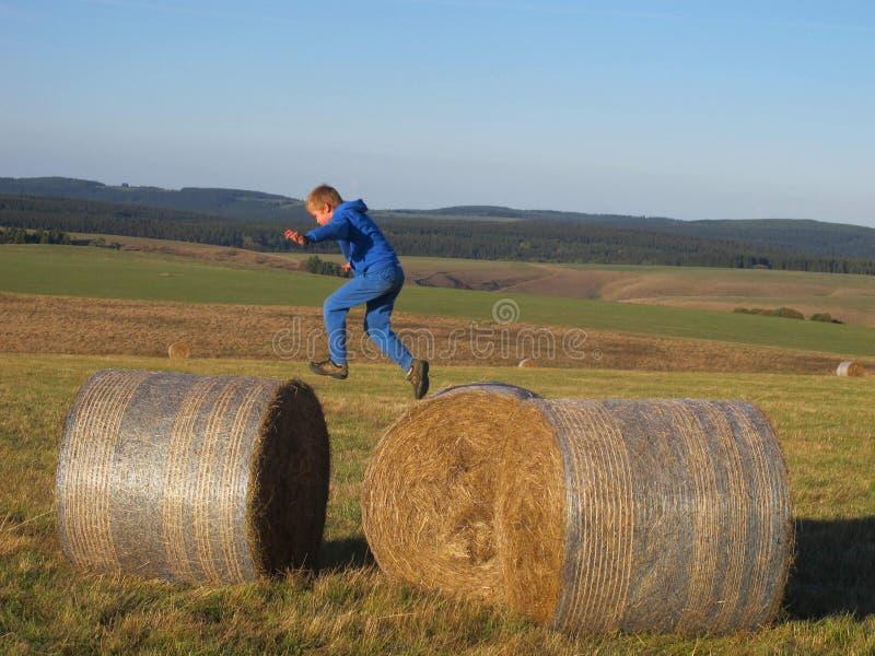 Мальчик скача на связки соломы стоковая фотография