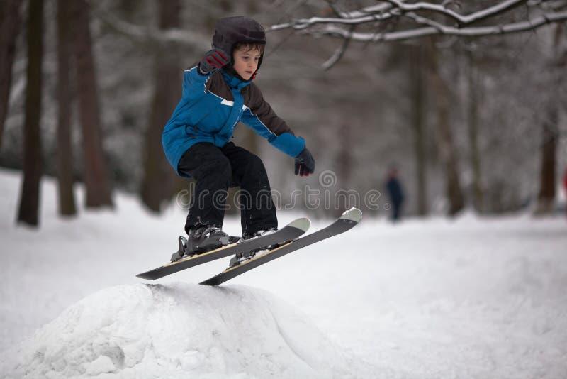 мальчик скачет меньший лыжник лыжи стоковые изображения
