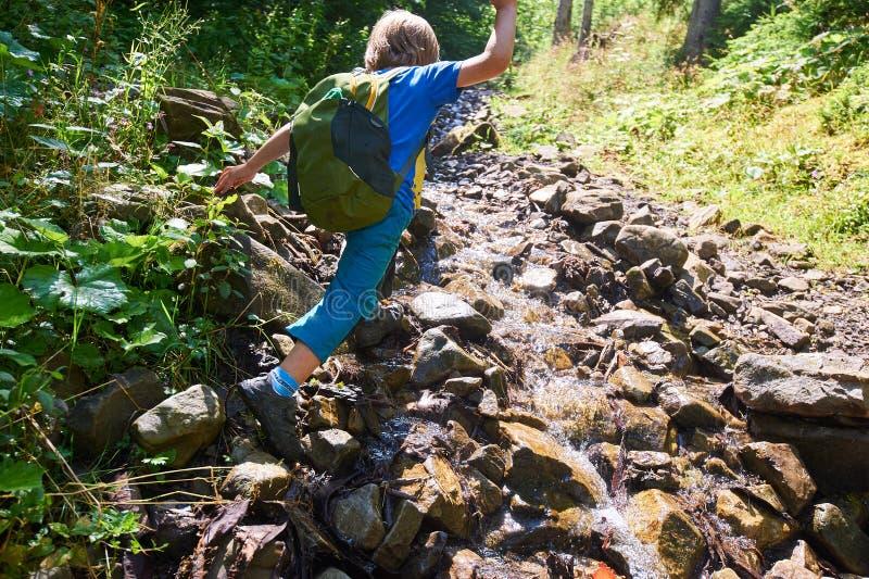 Мальчик скачет над потоком в лесе стоковые фото