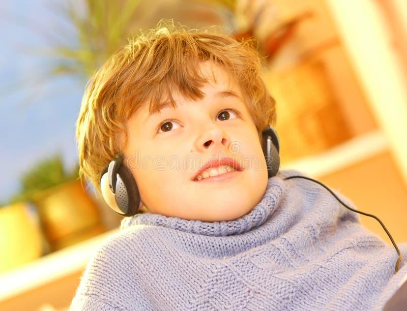 мальчик слушает нот к стоковое изображение rf