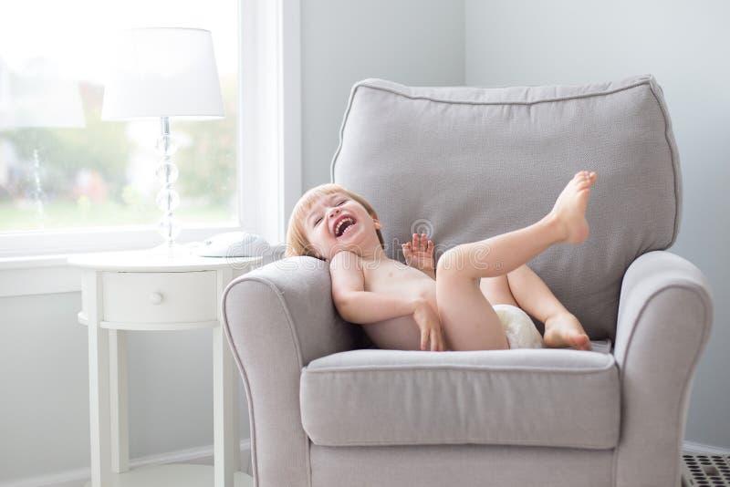Мальчик смеясь в пеленке стула нося стоковое изображение rf