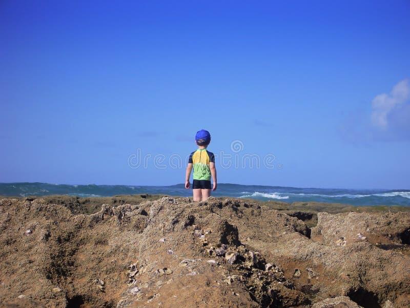 мальчик смотря вне море к стоковое изображение