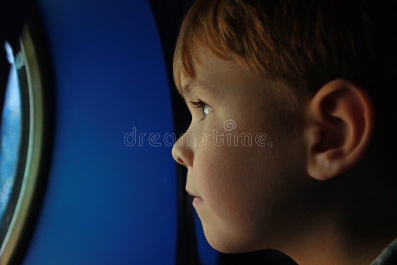 мальчик смотря профиль s porthole стоковые фото