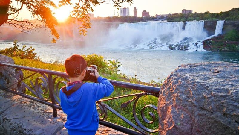 Мальчик снимает солнце утра Ниагарского Водопада стоковые фото