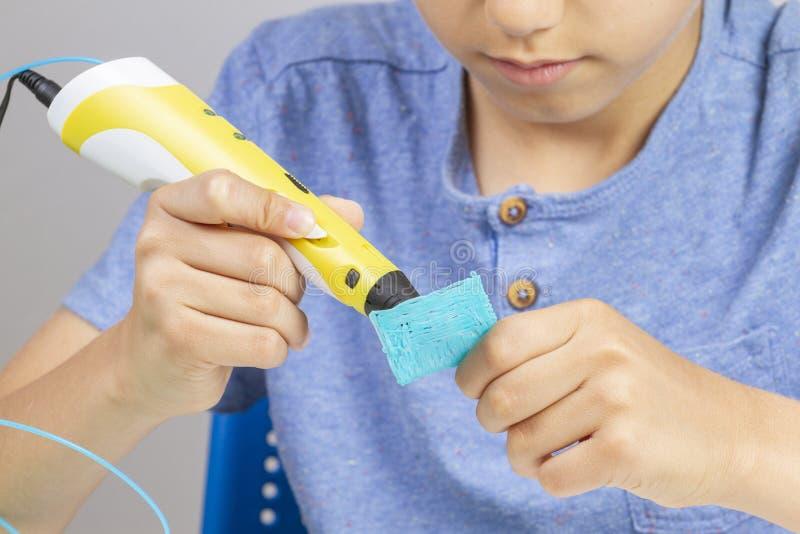 Мальчик создаваясь с деталем ручки печатания 3d новым стоковая фотография