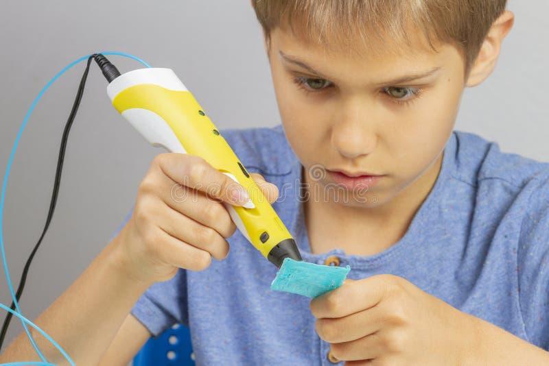 Мальчик создаваясь с объектом ручки печатания 3d новым стоковое изображение rf