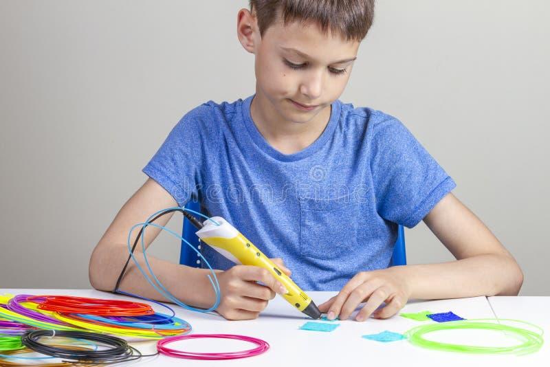 Мальчик создаваясь с объектом ручки печатания 3d новым стоковые фото