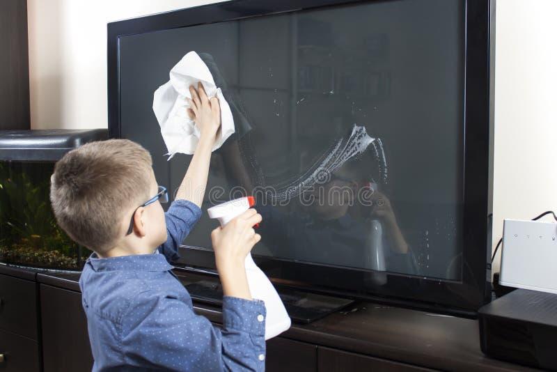 Мальчик со стеклами во время чистки Он обтирает экран ТВ с пылью от ткани стоковое фото rf