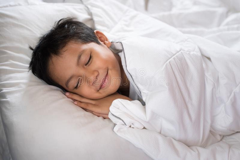Мальчик спать с стороной улыбки на белых простыне и подушке стоковая фотография rf