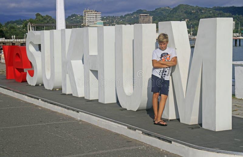 Мальчик стоит на письмах с именем города Сухуми стоковое фото