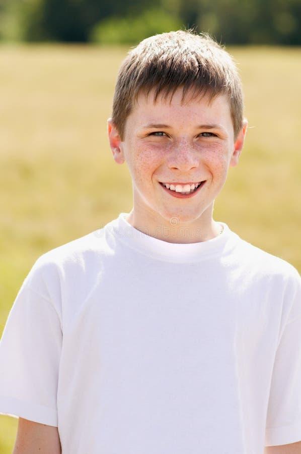 Мальчик стоит на поле стоковое фото