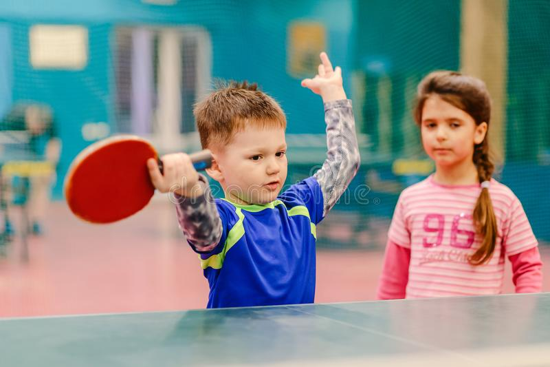 Мальчик стоя в зале тенниса, распространяя его руки к сторонам зала тенниса, ракетка тенниса, настольный теннис стоковое фото rf