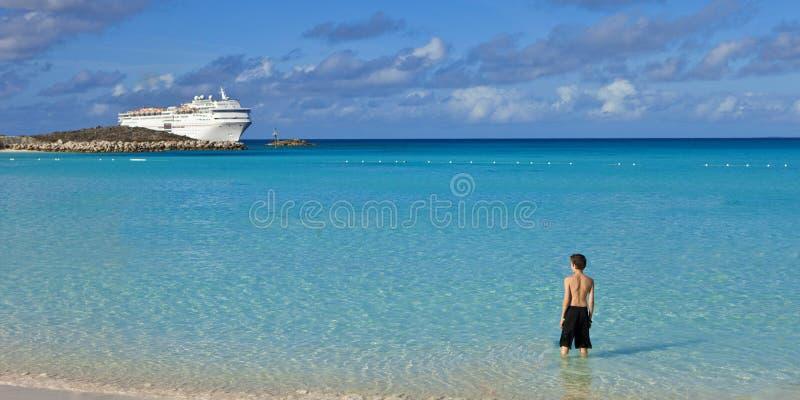 Мальчик стоя на тропическом пляже с туристическим судном стоковые фотографии rf