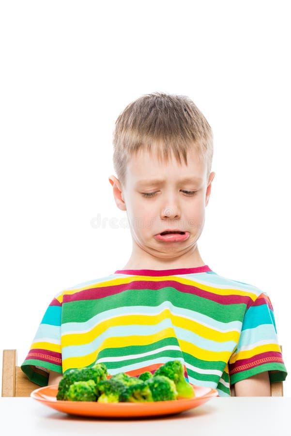 Мальчик с взглядами отвращения на плите брокколи, портрета на белой предпосылке стоковые изображения