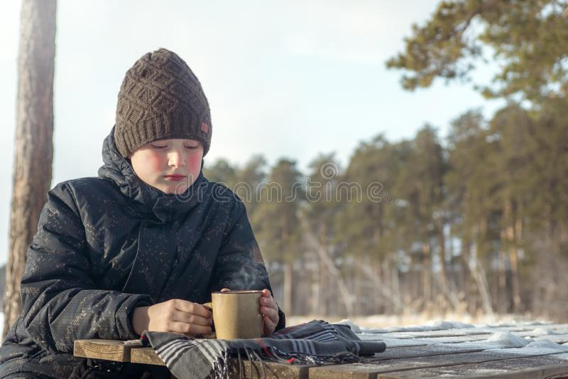 Мальчик с горячим напитком зимы на открытом воздухе стоковые фотографии rf