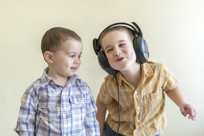 Мальчик с его наушниками танцует с его братом 2 маленьких брать в рубашках забавляют и танцуют стоковые изображения rf