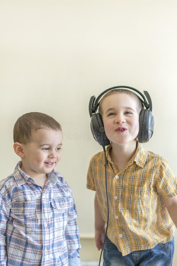 Мальчик с его наушниками танцует с его братом 2 маленьких брать в рубашках забавляют и танцуют стоковое изображение