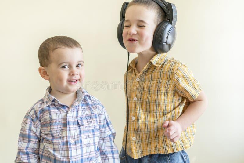 Мальчик с его наушниками танцует с его братом 2 маленьких брать в рубашках забавляют и танцуют 2 стоковые изображения rf