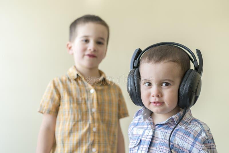 Мальчик с его наушниками танцует с его братом 2 маленьких брать в рубашках забавляют и танцуют мужчина стоковые изображения rf