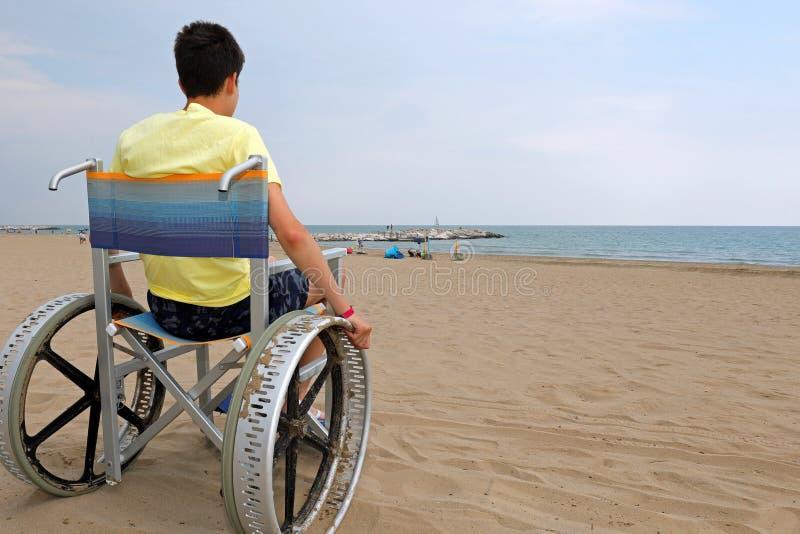 Мальчик с желтой рубашкой на пляже на инвалидной коляске стоковые фотографии rf