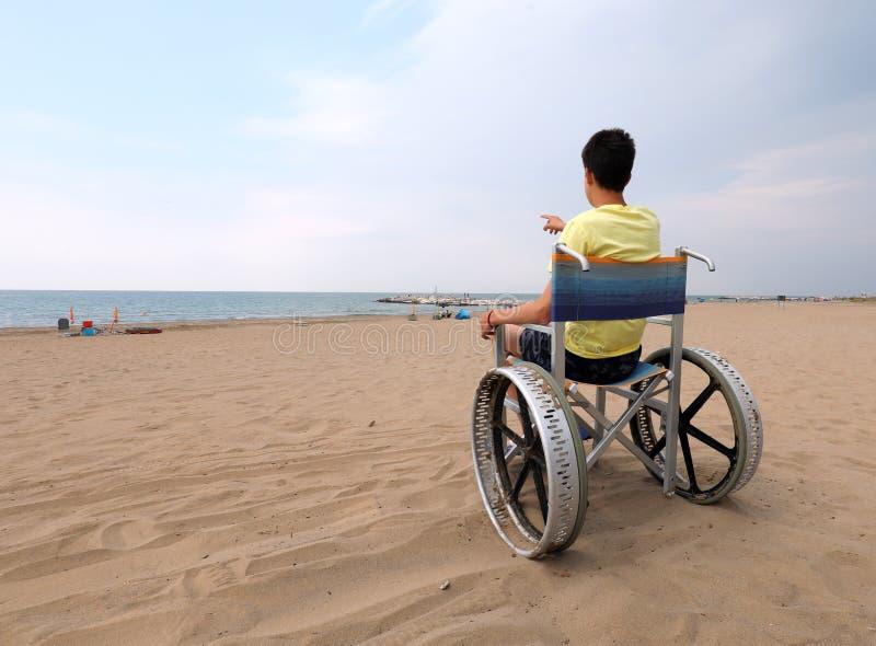 Мальчик с жёлтым жилетом на инвалидной коляске стоковые фотографии rf