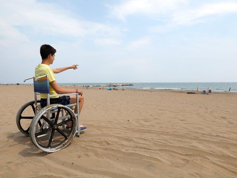 Мальчик с жёлтым жилетом на коляске на пляже стоковая фотография