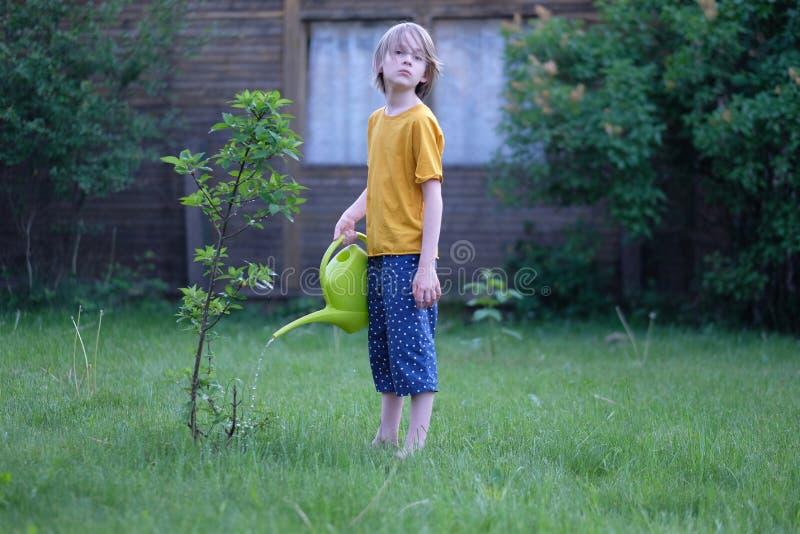 Мальчик с моча чонсервной банкой в его руках стоковые фото