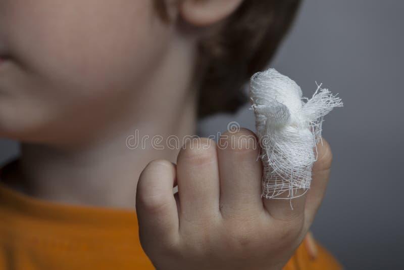 Мальчик с перевязанной раной на его пальце стоковые фотографии rf