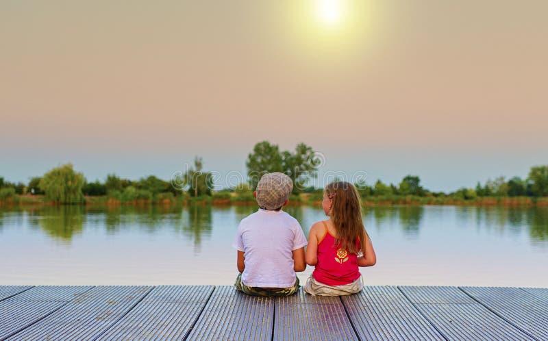 Мальчик с плоской крышкой и маленькая девочка сидят на пристани Мальчик и девушка смотрят на золотом заходе солнца Влюбленность,  стоковые фотографии rf