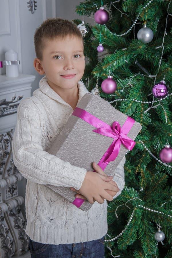 Мальчик с подарком рождества близко украсил treee стоковое фото rf