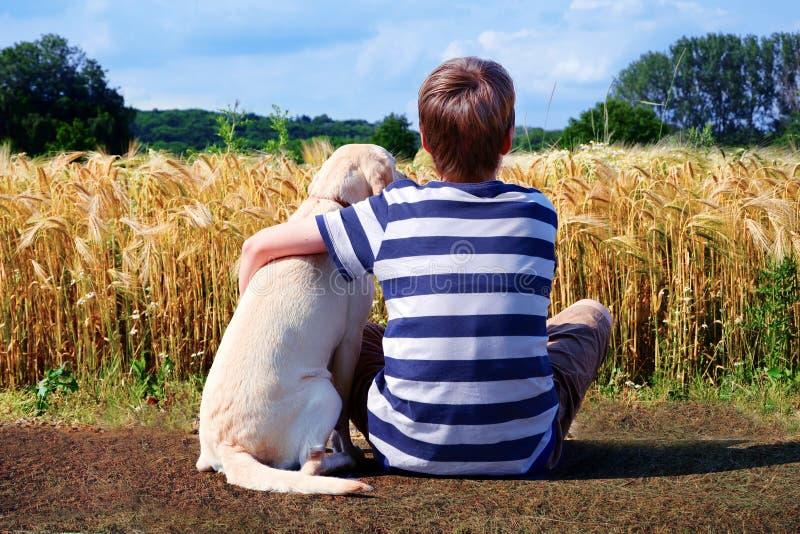 Мальчик с собакой любимчика стоковое изображение rf