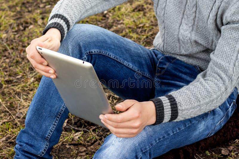Мальчик с таблеткой в его руках сидит на траве Читать в стоковое фото rf