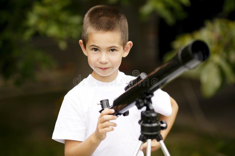 Мальчик с телескопом стоковые фотографии rf
