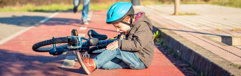 Мальчик с ушибом колена после падать, который нужно bicycle стоковые изображения